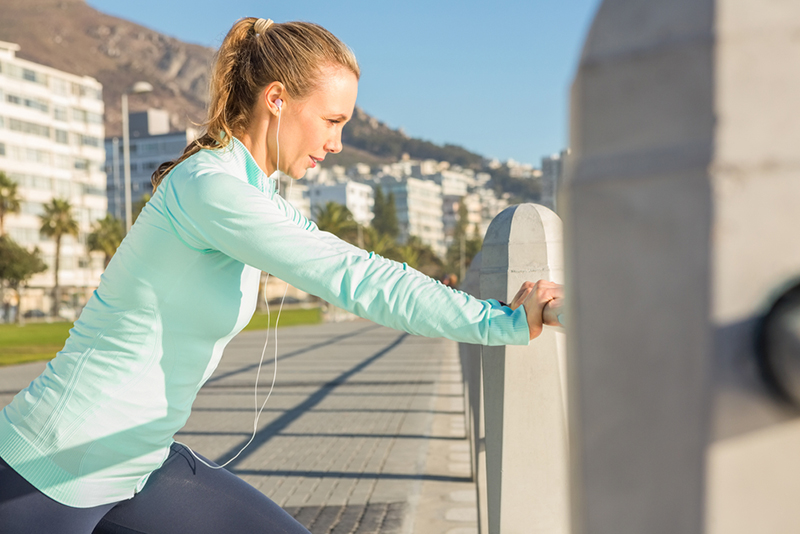 Fit blonde stretching on railing and listening to music at promenade