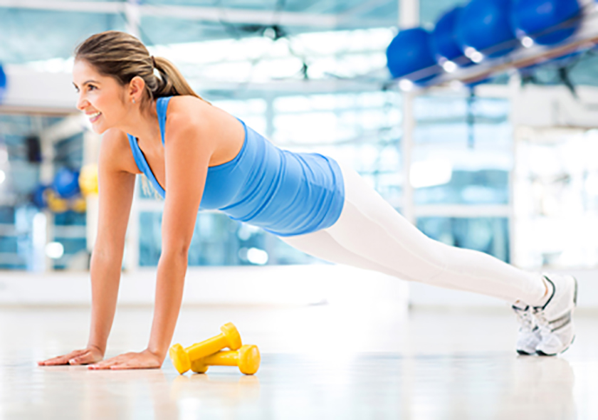 Athletic woman doing push-ups at the gym