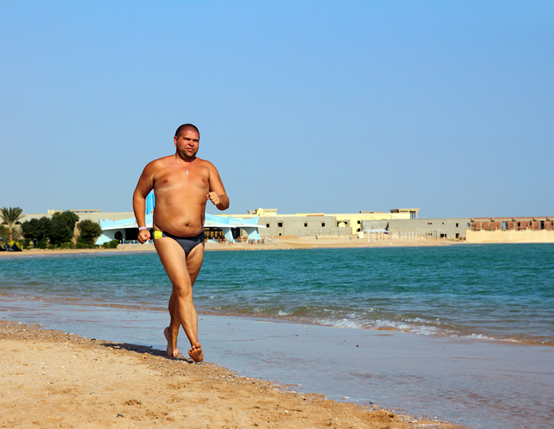 sport - overweight man running on sea coastline